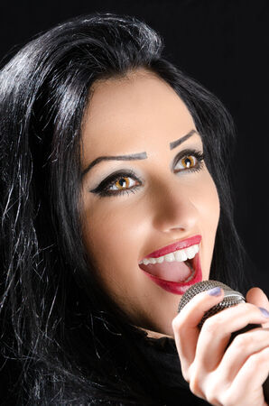 Happy girl singing with a microphone against a black background Stock Photo