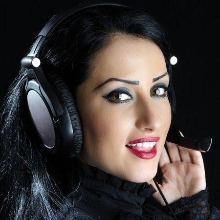 Attractive girl with headset against a black background Stock Photo