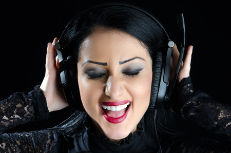 Attractive, happy girl with headphones against a black background