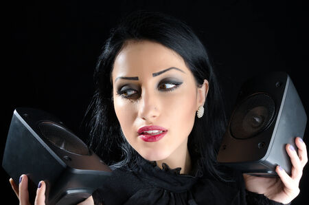 Attractive woman holding two audio speakers against a black background