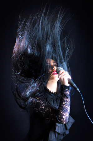 Brunette woman passionately singing with microphone throwing hair up in the air against a black background