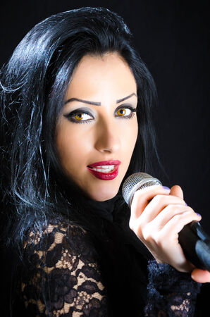 Attractive, brunette woman singing with a microphone against a black background