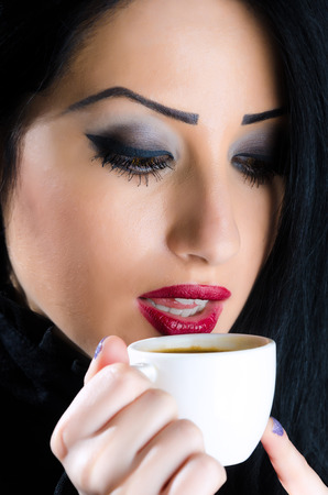 Young, attractive brunette woman holding a coffee cup to her lips