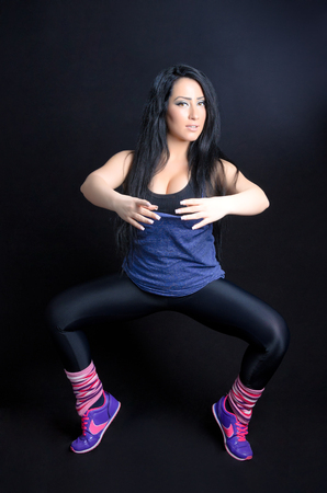 Attractive young woman working out in gym clothes against a black background