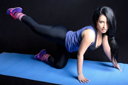 Attractive young woman doing exercise against a black background