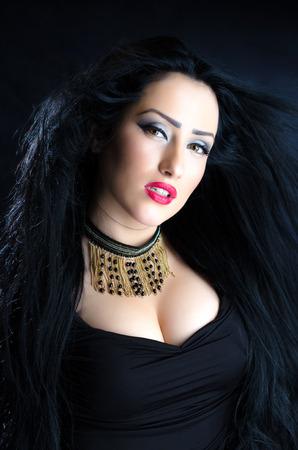 Portrait of glomorous brunette woman against a black background