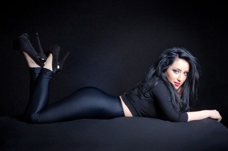 Sexy young woman giving a provocative pose against a black background Stock Photo