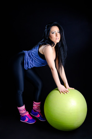 Attractive young woman posing in gym clothes with exercise ball against a black background Stock Photo