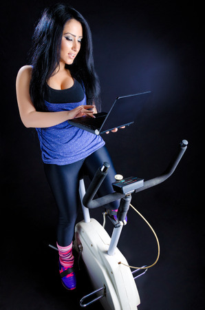 Young, attractive woman exercising on bike and working on laptop against a black background Stock Photo