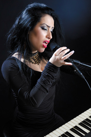 Attractive woman singing with microphone and keyboards against a black background Stock Photo