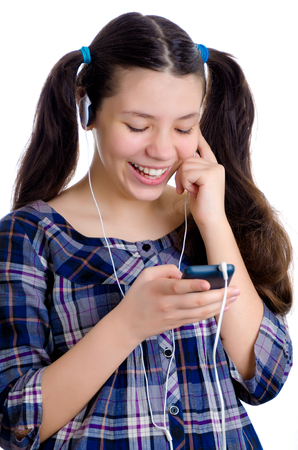 Happy female child isolated on white typing on phone while wearing headphones Stock Photo