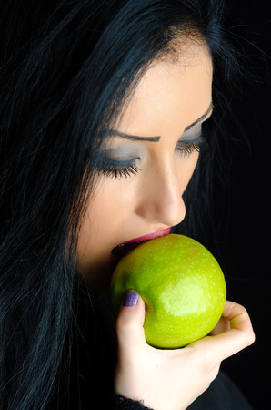 Beautiful brunette woman biting a green apple against a black background