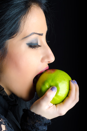 Attractive brunette woman biting a lipstick smeared green apple against a black background