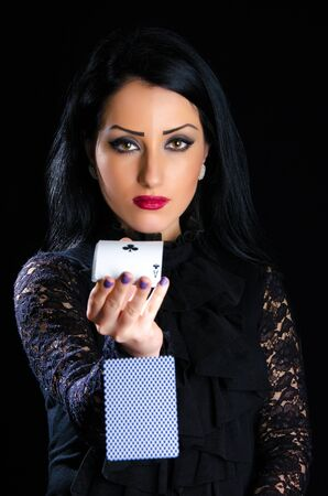 Attractive, elegant woman against black background throwing deck of cards Stock Photo