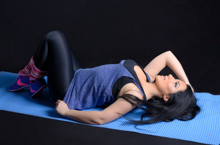 gym clothes: Attractive brunette woman posing in gym clothes against a black background