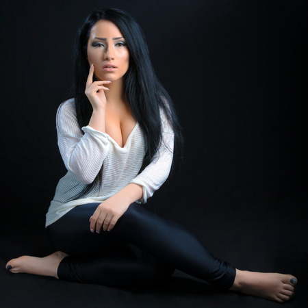 Attractive brunette woman posing against a black background