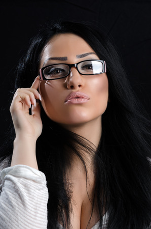 Beautiful brunette wearing reading glasses giving a provocative pose against a black background