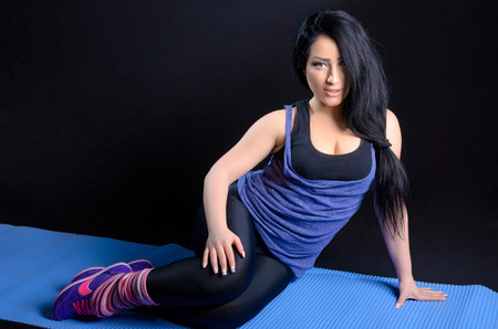 Attractive brunette woman posing in sport clothes against a black background