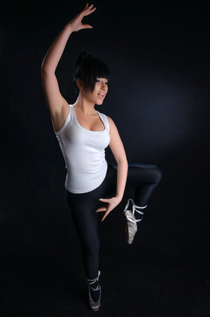 Attractive girl practicing ballet against a black background photo