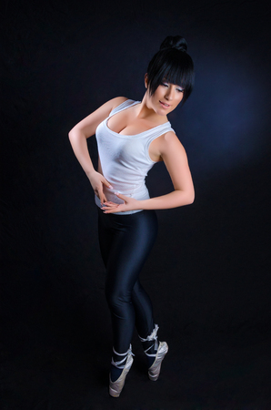 Attractive girl practicing ballet against a black background Stock Photo