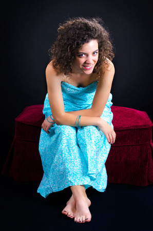 Attractive young curly woman posing barefoot against a black background