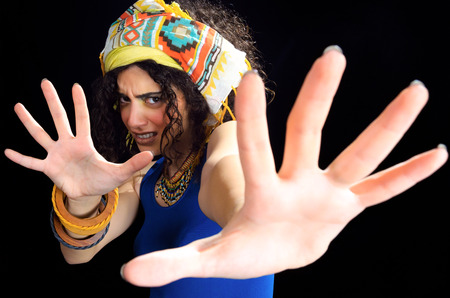 Frightened woman wearing ethnic clothes and extending hands