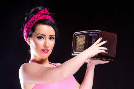 Pin-up style young woman holding a vintage radio against a black background