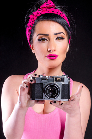 Pin-up style girl holding old camera against a black background
