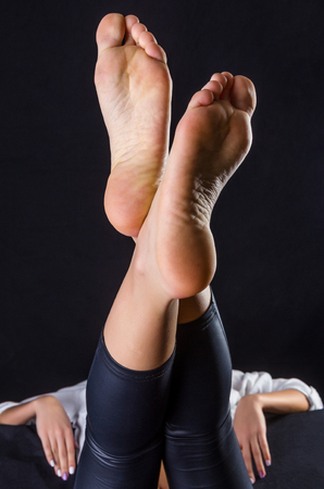 bare feet girl: Beautiful, clean female soles against a black background Stock Photo