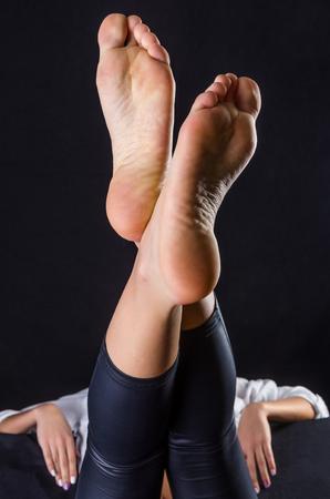 pies sexis: Hermosas mujeres, suelas limpias contra un fondo negro Foto de archivo