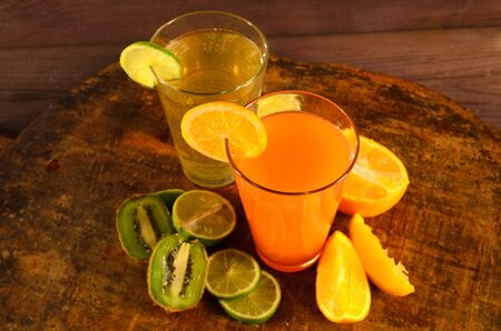 Orange, lime and kiwi juices on a wooden table