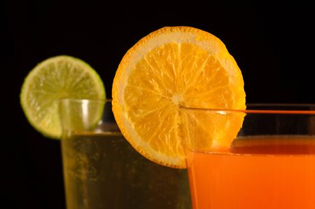 Orange and lime juices on a black background