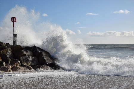 hengistbury: Waves crashing against the breakwater at Hengistbury Head, Dorset Stock Photo