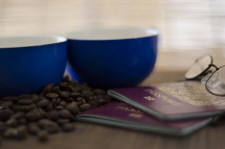 A tabletop scene with two dark blue coffee cups and coffee beans with two British passports and some ladies reading glasses  Stock Photo