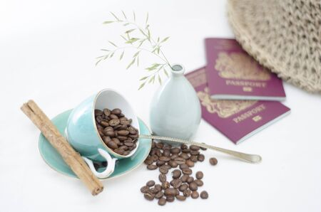 A tabletop scene with light blue coffee cup with coffee beans and cinnamon stick, two British passports and a summer straw hat and a small vase with some wild grass in