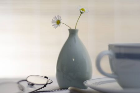 A bright and cheerful tabletop scene with a coffee cup, a vase with two Daisies a pair of black rimmed reading glasses with notepad and pen  photo