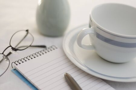 Bright clean cut table top scene with coffee cup, notepad and pen, reading glasses and vase base  photo