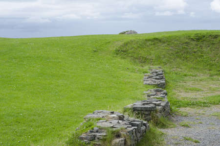 Ancient ruined castle wall curving around green grass meadow.
