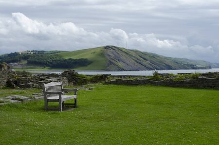 Empty wooden bench at view point overlooking rolling hills of coastal bay.