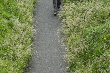 An ariel view of a persons legs walking on pathway between long summer grasses