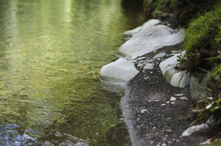 Calm Riverbank with Reflections on Water and Smooth Stones and Pebbles photo
