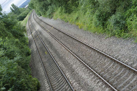 Railway tracks through English countryside at angle in summer