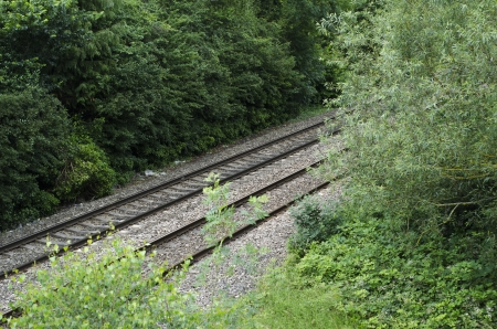 Railway tracks seen through trees and hedges in English countryside in summer