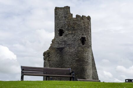 An empty wooden bench in the foreground with a castle ruin in the background  Stock Photo