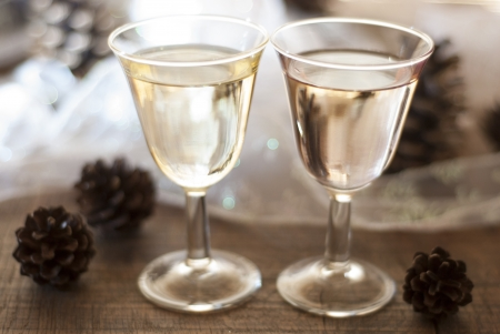 Two full celebratory wine glasses, in a glowing tabletop scene with christmas decorations  Stock Photo
