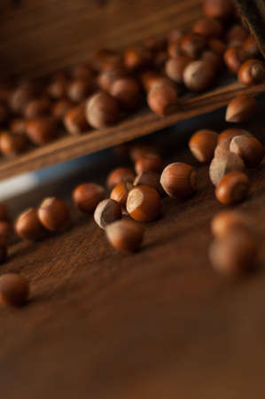 tumbling: Hazelnuts caught in motion tumbling from rustic wooden box