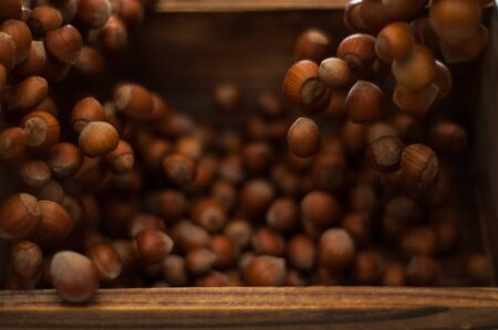 Hazelnuts caught in motion tumbling into rustic wooden box Stock Photo