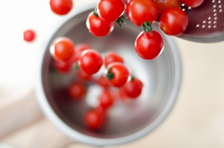 Ripe cherry tomatoes being tumbled and poured down from a metal colander into a silver metal pot with white background