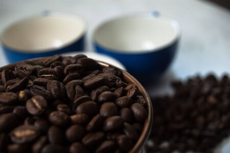 Closeup of coffee beans in a copper pot with indigo blue coffee cups