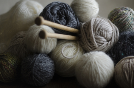 Closeup of balls of wool in muted, earthy colors with wooden knitting needles